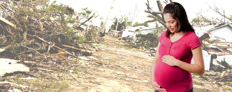 A pregnant woman looks down at her belly; behind her is an image of a house destroyed by a storm.