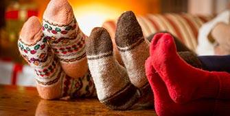 Closeup photo of family feet in wool socks at fireplace.