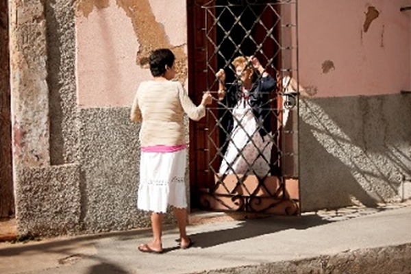 Two women stand talking at the front gate of a house.