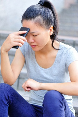 A young Asian woman sits on stairs outside. She is wearing blue pants, a grey t-shirt, and has her hair pulled back in a ponytail. Her left forearm is resting on her left knee and her right elbow rests on her right knee.  She holds her cell phone in her right hand and rests the top of the phone against her forehead. She appears to be deep in thought and perhaps sad..