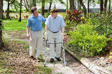 Younger man assisting an elderly man on a walk outside by a garden