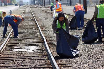 Responders cleaning around railroad tracks at a disaster site.