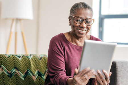 older woman smiling at the screen of the tablet she's holding