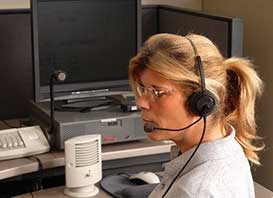 Emergency dispatcher on headset in front of a computer