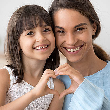 a young girl and her mother holding hands in the shape of a heart