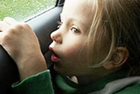 A young girl sitting in a car looking out the window at the rain