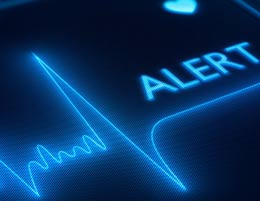 "A heart monitoring machine with the word ""ALERT"" on it"