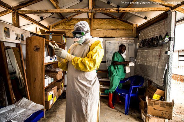 An Ebola worker putting on personal protective equipment